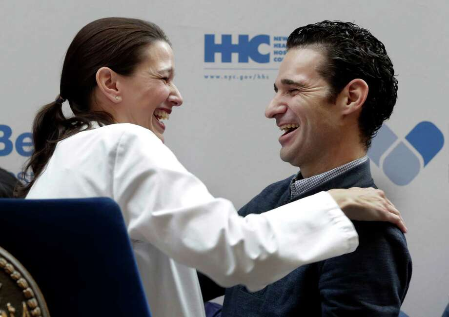 Dr. Craig Spencer, who was the first Ebola patient in New York City, is hugged by Dr. Laura Evans, director of Critical Care at Bellevue Hospital, during Tuesday's news conference announcing that he has been discharged. Photo: Richard Drew, STF / AP