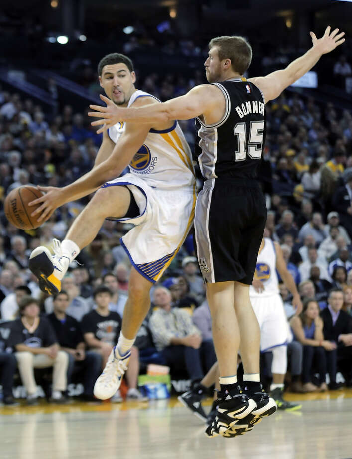 Klay Thompson (11), who returned from a one-game hiatus for a strained right hand, passes around San Antonio's Matt Bonner in the first half of the Warriors' 113-100 loss at Oracle Arena. Photo: Carlos Avila Gonzalez / The Chronicle / ONLINE_YES