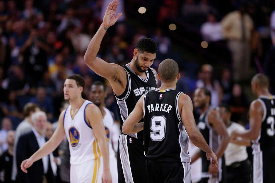 Tim Duncan celebrates with teammate Tony Parker in the closing minutes of the Spurs' 113-100 win over the Golden State Warriors. Photo: Marcio Jose Sanchez, STF / Associated Press / AP