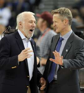 Spurs head coach Gregg Popovich, left, and Warriors head coach Steve Kerr, right, share a few words before the beginning of the teams' game on Nov. 11, 2014.