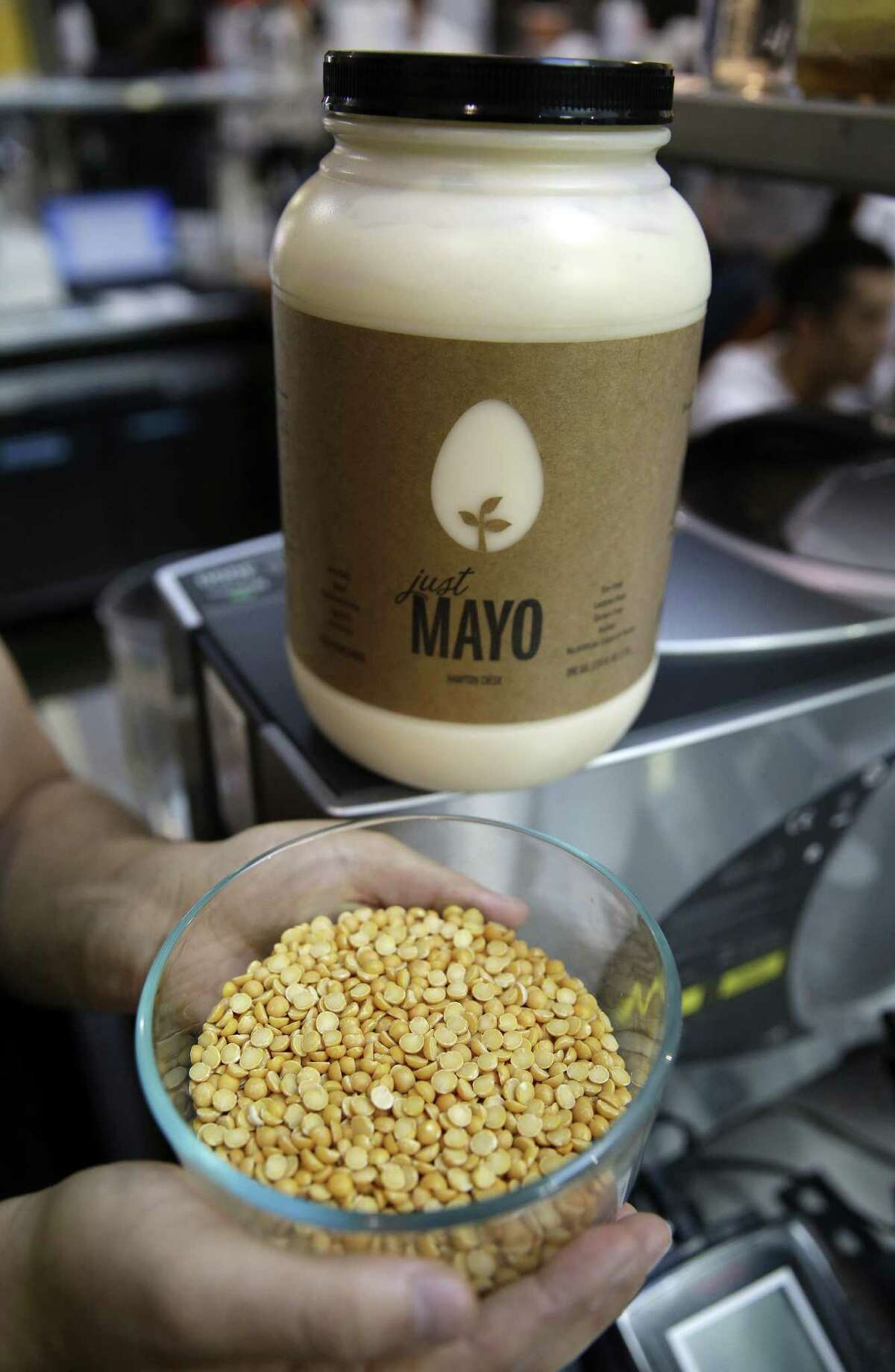 """FILE - In this Dec. 3, 2013 file photo, Hampton Creek CEO and Founder Josh Tetrick poses with a bowl of a species of yellow pea used to make Just Mayo, a plant-based mayonnaise, at Hampton Creek Foods in San Francisco. Hellmann's mayonnaise owner Unilever on Oct. 31, 2014 filed a lawsuit against Hampton Creek for labeling its egg-free product """"Just Mayo,"""" saying that federal regulators and dictionaries define mayonnaise as a spread that contains eggs. (AP Photo/Eric Risberg, File) ORG XMIT: MER2014111115223909"""