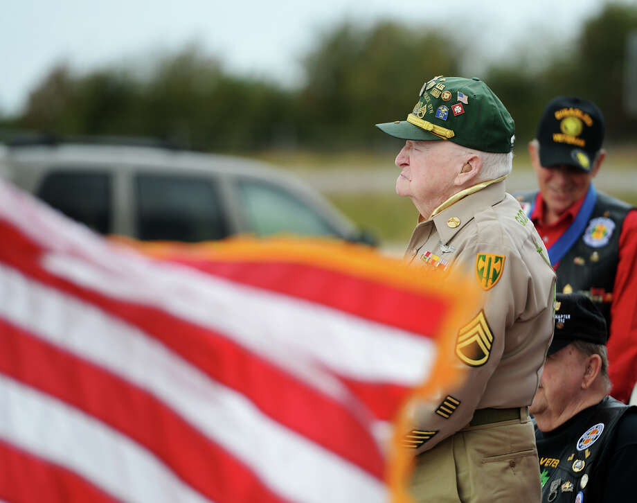 An American flag waves while Charles Henson and other veterans stand to be recognized Tuesday morning. The Vietnam Veterans of America, Inc, Southeast Texas Chapter #292, sponsored a Veterans Day observance at the Ben J. Rogers Regional Visitors Center on Tuesday.