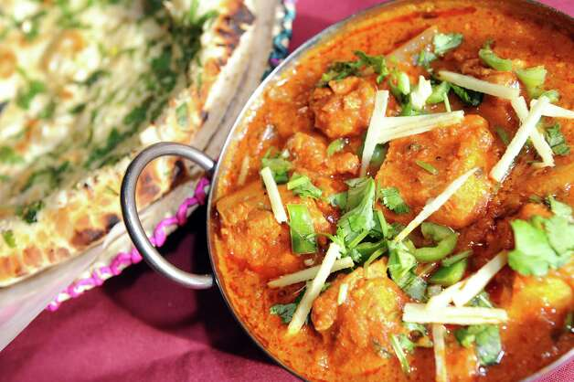 Chicken Tikka Masala is marinated and served with onions, tomatoes and green peppers and a side of garlic naan on Wednesday, Nov. 5, 2014, at Kabab Masala in Halfmoon, N.Y. (Cindy Schultz / Times Union) ORG XMIT: MER2014110517413526 Photo: Cindy Schultz / 00029354A
