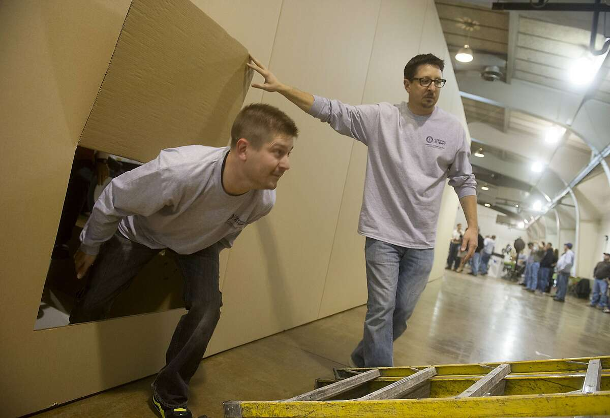 Thinking out of the box: Troy Little, the director of design for York Container, holds open the escape hatch of cardboard structure for fellow designer Jamie Laughman in the York Expo Center in York, Pa. They were attempting to build the world's largest cardboard box.