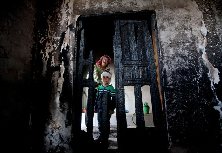 Palestinians inspect damages of a mosque following an attack in the West Bank village of Mughayer, near Ramallah. The village mayor blamed Jewish settlers. Photo: Majdi Mohammed / Associated Press / AP