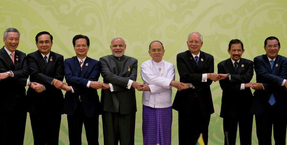 Indian Prime Minister Narendra Modi, fourth from left, poses for a group photo with leaders of the Association of Southeast Asian Nations (ASEAN) during the 12th ASEAN-India summit at Myanmar International Convention Center in Naypyitaw, Myanmar, Wednesday, Nov. 12, 2014. Leaders from left, Singaporean Prime Minister Lee Hsien Loong, Thailand's Prime Minister Prayuth Chan-ocha, Vietnamese Prime Minister Nguyen Tan Dung, Modi, Myanmar President Thein Sein, Malaysian Prime Minister Najib Razak, Sultan of Brunei Hassanal Bolkiah, Cambodian Prime Minister Hun Sen. (AP Photo/Gemunu Amarasinghe) Photo: Gemunu Amarasinghe / Associated Press / AP