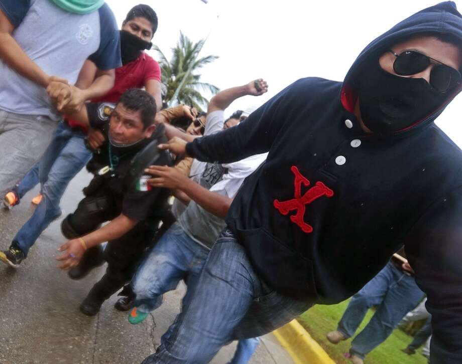Protesters hold a riot police during clashes following a protest against the suspected massacre of 43 missing students, near the airport in Acapulco. Photo: PEDRO PARDO / AFP/Getty Images / AFP