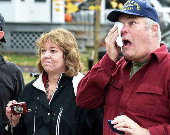 Kathleen Van Acken holds her emotions in check while her husband, David, wipes tears from his eyes Wednesday morning Nov. 12, 2014, as they watch while the tree they donated to the state is removed from their Schenectady, N.Y., home.    The tree will become the state Christmas tree and reside on the Empire State Plaza. The official lighting will be at 5:15 p.m. Dec. 7.     (Skip Dickstein/Times Union) Photo: SKIP DICKSTEIN / 00029428A