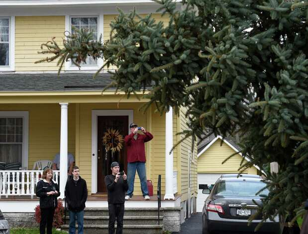 Kathleen Van Acken, left, with her sons Kevin Van Acken, second from left,and  Mike Cardillo and her husband, David, watch their blue spruce leave on a flatbed truck Wednesday, Nov. 12, 2014. from their Schenectady, N.Y., home. (Skip Dickstein/Times Union) Photo: SKIP DICKSTEIN / 00029428A