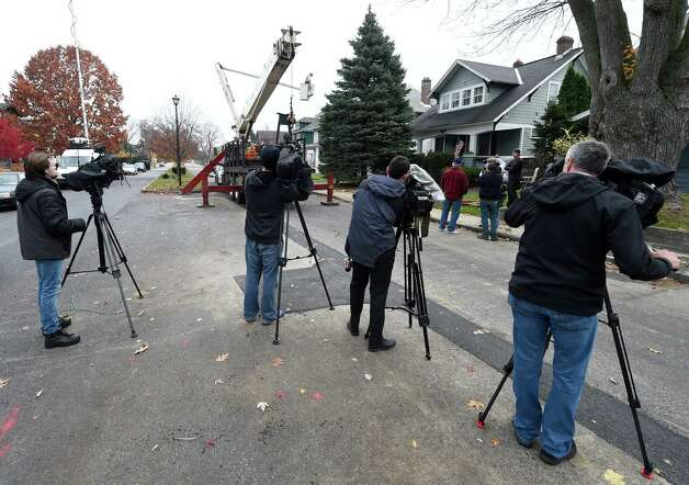 News crews record the cutting of the donated tree Wednesday morning Nov. 12, 2014, that was removed from 834 Woodland Avenue in Schenectady, N.Y.  The tree will become the state Christmas tree and reside on the Empire State Plaza.  (Skip Dickstein/Times Union) Photo: SKIP DICKSTEIN / 00029428A