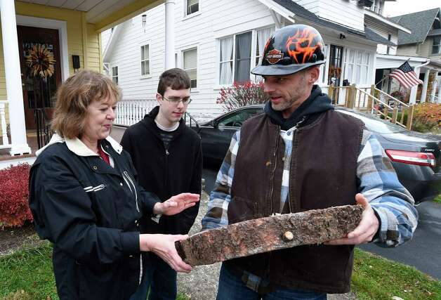 State Office of General Services grounds crew member Jeremy Jasper gives a piece of the blue spruce removed from 834 Woodland Ave. on Nov. 12, 2014, to owner Kathleen VanAcken in Schenectady, N.Y.  With her is her son Kevin VanAcken   (Skip Dickstein/Times Union) Photo: SKIP DICKSTEIN / 00029428A