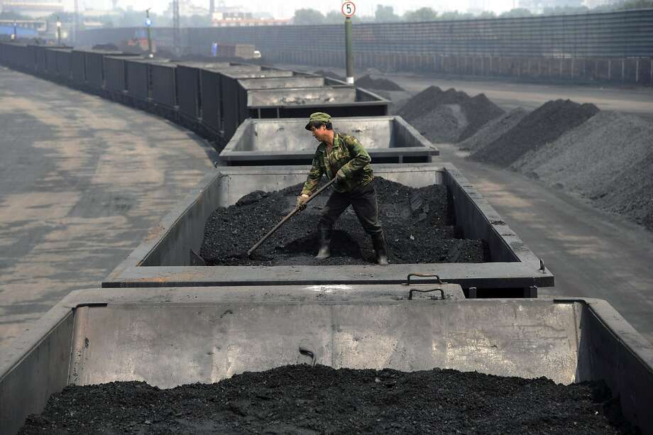 FILE - In this Wednesday, July 31, 2013, file photo, a worker levels the coal on a freight train in Taiyuan in northern China's Shanxi province. Spurred chiefly by China, the United States and India, the world spewed far more carbon pollution into the air last year than ever before, scientists announced Sunday, Sept. 21, 2014, as world leaders gather to discuss how to reduce heat-trapping gases.  (AP Photo/File) CHINA OUT Photo: Uncredited, Associated Press