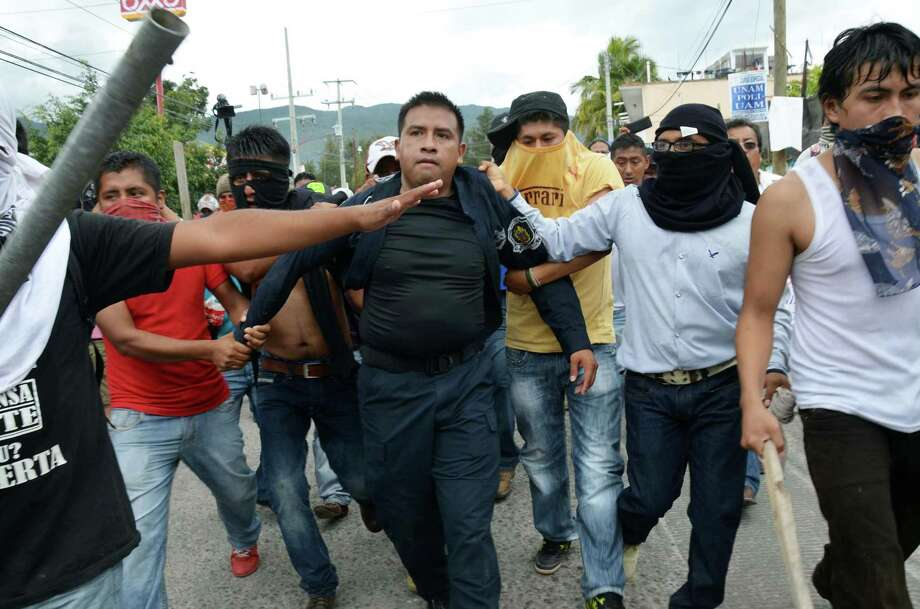 Masked teachers detain a police officer during clashes in Chilpancingo, the capital of Guerrero state, Mexico, Tuesday, Nov. 11, 2014. Supporters of 43 missing college rural students, refusing to believe they are dead, have kept up the protests that have blocked major highways and set government buildings ablaze in recent weeks. The students disappeared at the hands of a city police force on Sept. 26 in the town of Iguala. (AP Photo/Alejandrino Gonzalez) Photo: Alejandrino Gonzalez, STR / AP