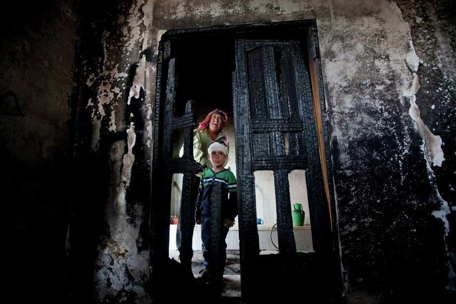 Palestinians inspect a mosque damaged in an attack early Wednesday in the West Bank village of Mughayer. Its mayor blamed Jewish settlers. Late Tuesday night, a fire did light damage to a synagogue in the Israeli-Arab town of Shfaram. Photo: Majdi Mohammed, STR / AP