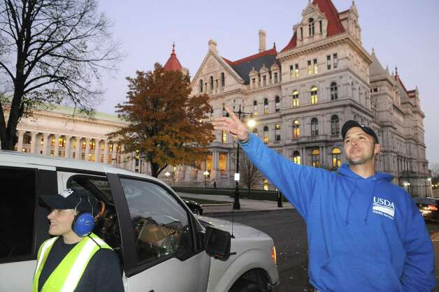 USDA biologist Bryan Haslun, right, and wildlife specialist Angela Kolewe disperse crows from the buildings around the Capitol on Wednesday Nov. 12, 2014 in Albany, N.Y. (Michael P. Farrell/Times Union) Photo: Michael P. Farrell / 00029400A