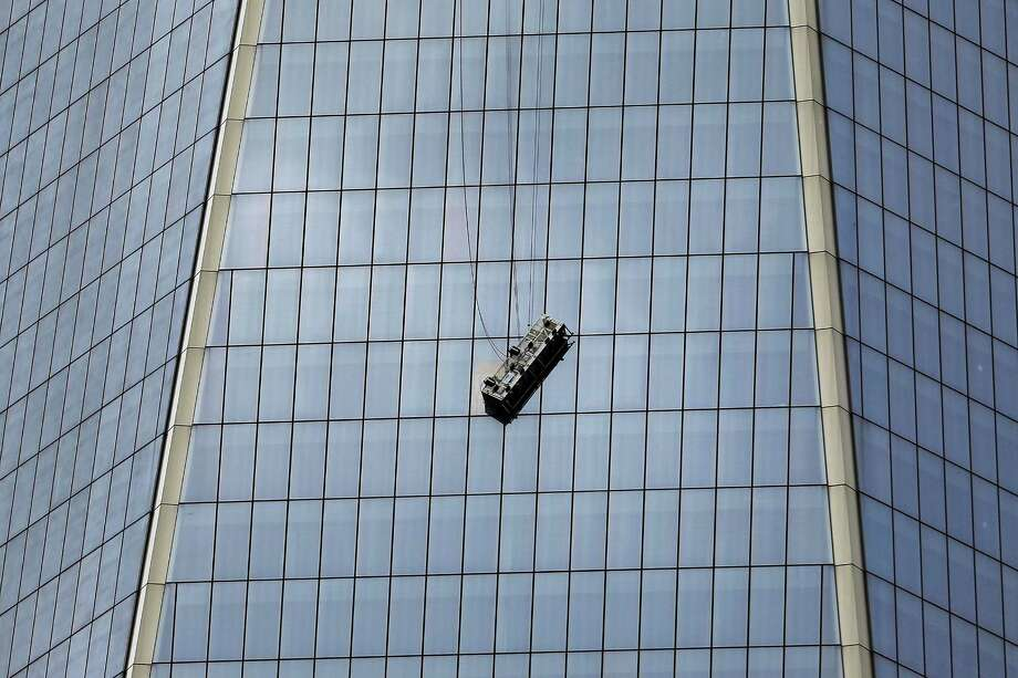 NEW YORK, NY - NOVEMBER 12:  A scaffold carrying two workers hangs 69 floors up at One World Trade Center on November 12, 2014 in New York City.  The workers were washing windows 69 floors up soon after 1 World Trade Center, the tallest building in the Western Hemisphere, opened. (Photo by Spencer Platt/Getty Images) Photo: Spencer Platt, Staff / 2014 Getty Images