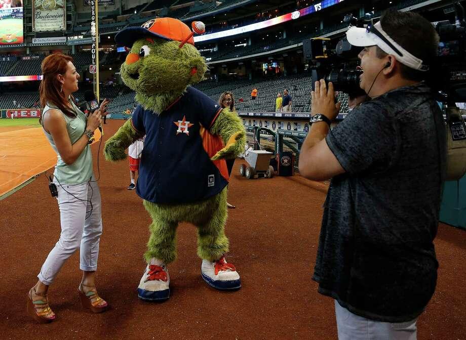 Sports reporter Julia Morales, with Comcast Sports Net, jokes around with Orbit at Minute Maid park, Saturday, June 14, 2014, in Houston.  ( Karen Warren / Houston Chronicle  ) Photo: Karen Warren, Staff / © 2014 Houston Chronicle