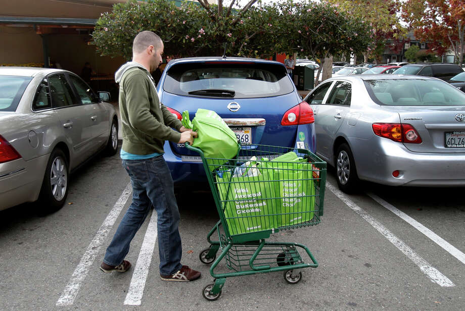 Yonatan Schkolnik brings groceries to his car in the parking lot of Whole Foods for his Instacart delivery. Photo: Brant Ward / The Chronicle / ONLINE_YES