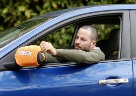 Yonatan Schkolnik adjusts his Sidecar identification bib around his side view mirror Monday November 10, 2014. Yonatan Schkolnik drives paying customers for Sidecar and delivers groceries for Instacart in the Bay Area.