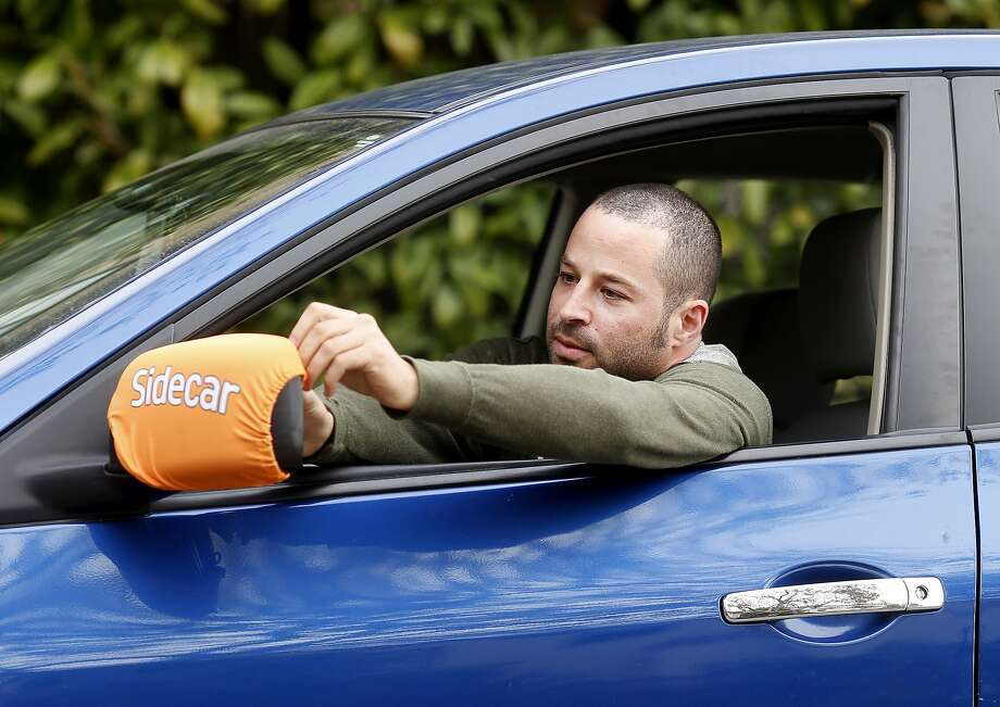 Yonatan Schkolnik adjusts his Sidecar identification bib around his side view mirror Monday November 10, 2014. Yonatan Schkolnik drives paying customers for Sidecar and delivers groceries for Instacart in the Bay Area. Photo: Brant Ward, The Chronicle