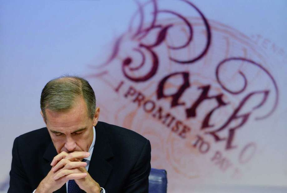 """Bank of England Governor Mark Carney holds a press conference on the quarterly report on the country's economy at his office in London, Wednesday Nov. 12, 2014. Carney says inflation is """"more likely than not"""" to continue to fall below one percent in the next six months and that growth will be slightly weaker due to a global slowdown. (AP Photo/Stefan Rousseau, Pool) Photo: Stefan Rousseau, POOL / PA POOL"""