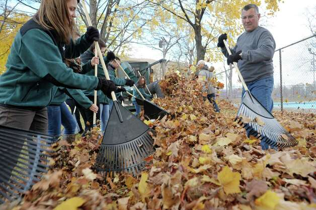 "Kelly Sullivan, left, TrustCo Bank marketing coordinator and Tom Poitras, right, vice president of the bank work with other bank employees and Schenectady Parks Department workers as they clean up leaves at Quackenbush Park Wednesday, Nov. 12, 2014, in Schenectady, N.Y. TrustCo Bank officials held an unveiling at the park to show off the over $20,000 in improvements made and funded by the bank.  Rob McCormick, president and CEO of Trustco said that they wanted to help out in neighborhoods and they reached out to the mayor and then met with the neighborhood association. ""We see these neighborhoods as our neighborhoods,"" McCormick said. Along with resurfacing the basketball court, new picnic tables, benches and garbage cans were purchased for the park.  McCormick said that the plan is to return to the park in the spring to repair any damage from winter and then decide on the next park to work on.  (Paul Buckowski / Times Union) Photo: Paul Buckowski / 00029457A"