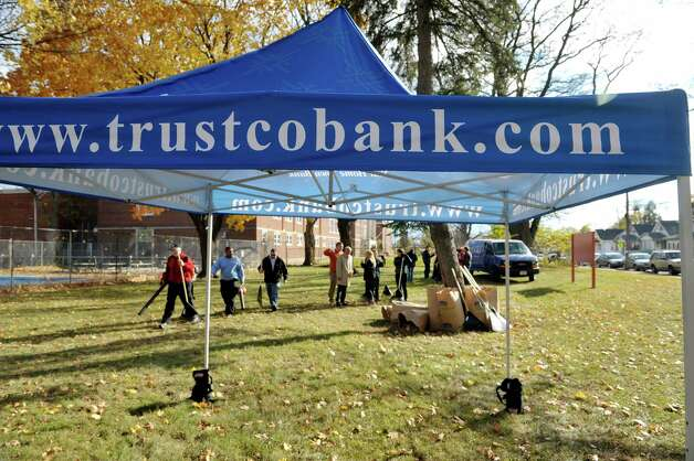 "TrustCo Bank employees work cleaning up Quackenbush Park on Wednesday, Nov. 12, 2014, in Schenectady, N.Y. TrustCo Bank officials held an unveiling at the park to show off the over $20,000 in improvements made and funded by the bank. Rob McCormick, president and CEO of Trustco said that they wanted to help out in neighborhoods and they reached out to the mayor and then met with the neighborhood association.  ""We see these neighborhoods as our neighborhoods,"" McCormick said. Along with resurfacing the basketball court, new picnic tables, benches and garbage cans were purchased for the park. McCormick said that the plan is to return to the park in the spring to repair any damage from winter and then decide on the next park to work on.  (Paul Buckowski / Times Union) Photo: Paul Buckowski / 00029457A"