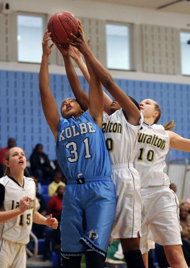 Kolbe Cathedral's Cherelle Moore and Lauralton Hall's Keylantra Langley and Kristina McCathy battle for the rebound during the South-West Conference semi-final game Wednesday Feb. 24, 2010 at Oxford High School. Photo: Autumn Driscoll / Connecticut Post