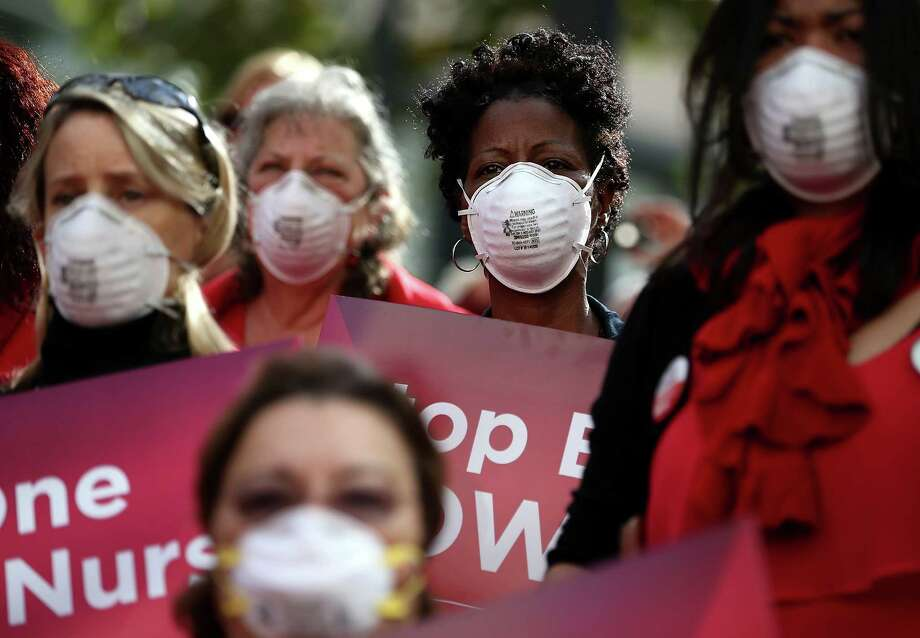 Nurses wear masks and hold signs Wednesday during a demonstration outside of the Dellums Federal Building in Oakland, California. Hundreds of nurses  pointed to lack of training and protective equipment to fight the Ebola virus.  Photo: Justin Sullivan, Staff / 2014 Getty Images