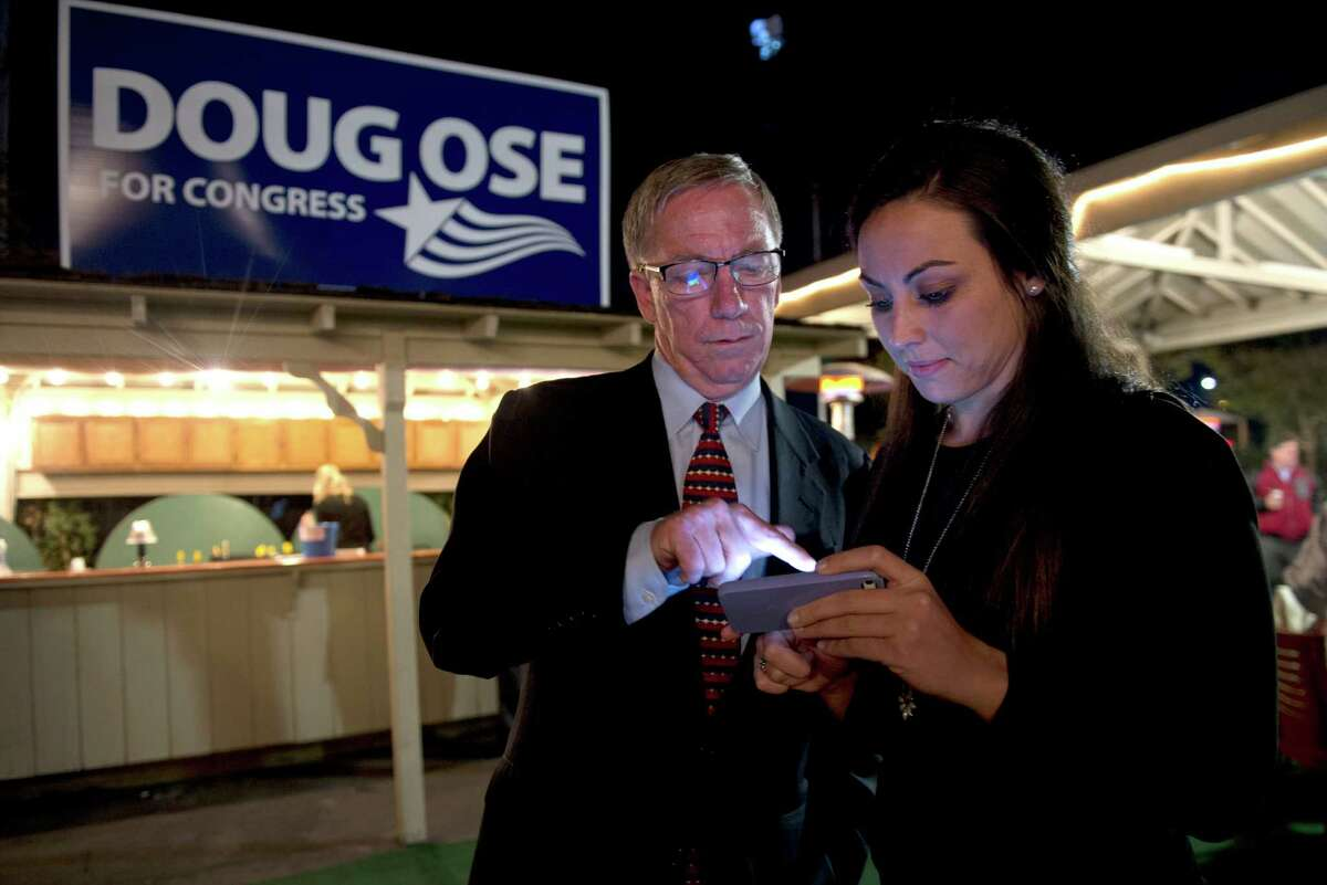 Former GOP Rep. Doug Ose, left, goes over results with Michawn Rich, right, communications director, as he waits for results with supporters at Rudy's Hideaway on Tues., Nov. 4, 2014, in Rancho Cordova, Calif. He is challenging Democratic Rep. Ami Bera for his seat in Congress District 7. (AP Photo/The Sacramento Bee, Renee C. Byer)