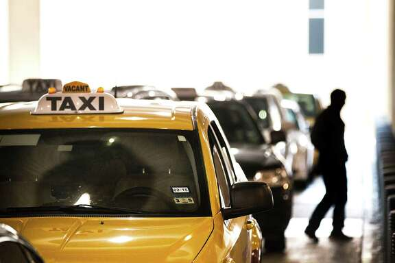 A cabdriver awaits passengers at Bush Intercontinental Airport, where services like Uber can now operate.