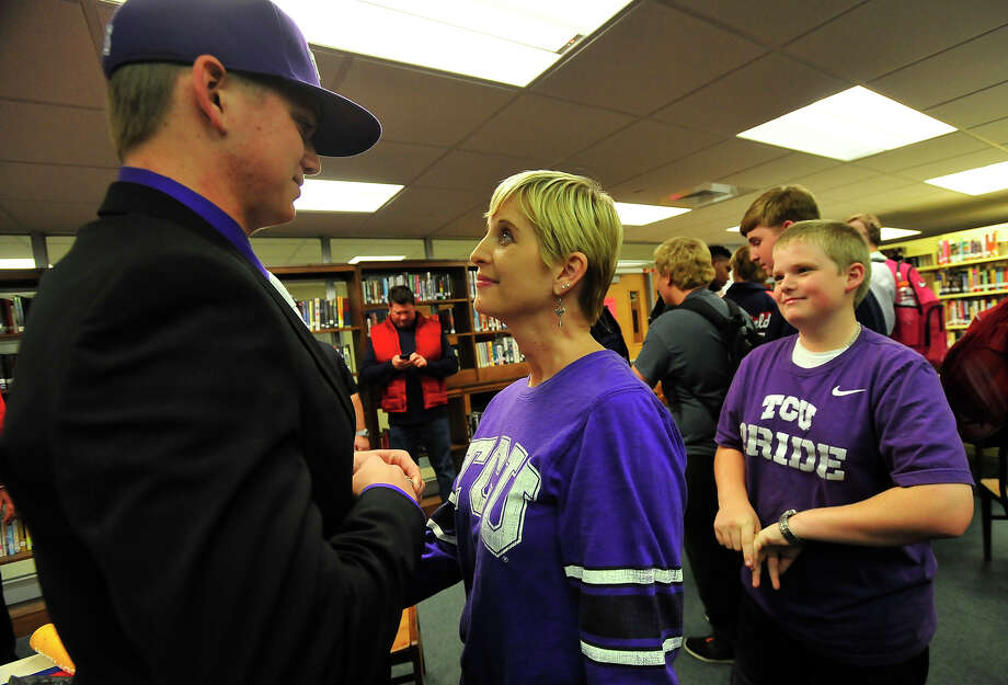 Devon Roedahl, 17, a senior at West Brook High School, shares a moment with his mother Mary Roedahl as younger brother Cole, 13, looks on after officially signing his commitment papers to attend TCU and join their baseball team Wednesday. Photo taken Wednesday, November 12, 2014 Kim Brent/@kimbpix Photo: KIM BRENT / Beaumont Enterprise