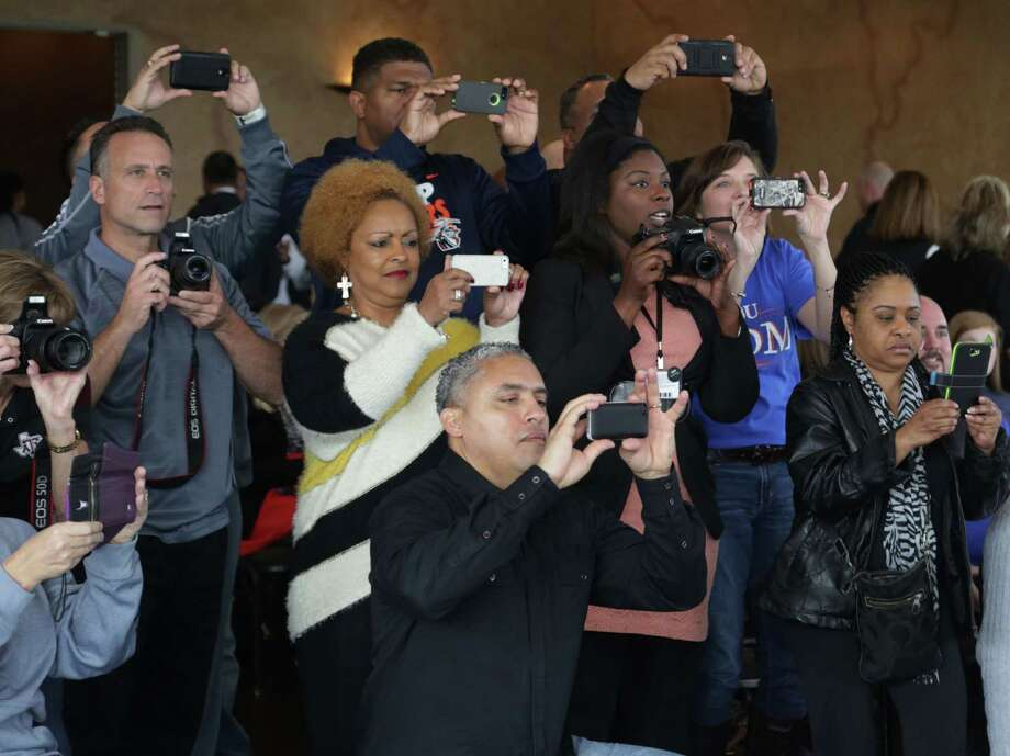 Picking a college isn't a snap decision, and that's why parents at the Humble ISD signing ceremony wanted to record the moment. Photo: Billy Smith II, Staff / © 2014 Houston Chronicle