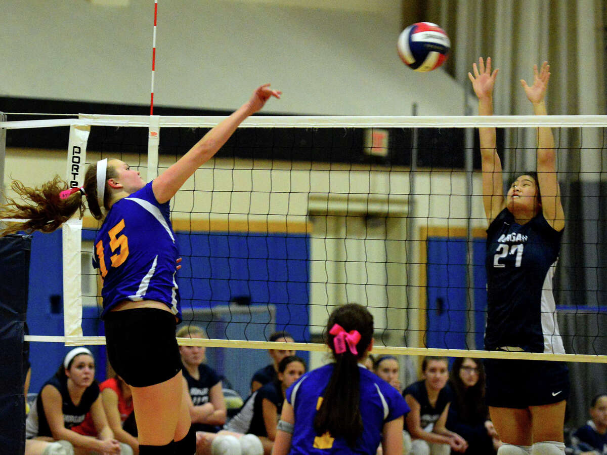 Seymour's Jesica Litwa spikes the ball as Morgan's Vivian Tran tries to block, during Class S girls volleyball semifinal action in East Haven, Conn. on Wednesday Nov. 12, 2014.