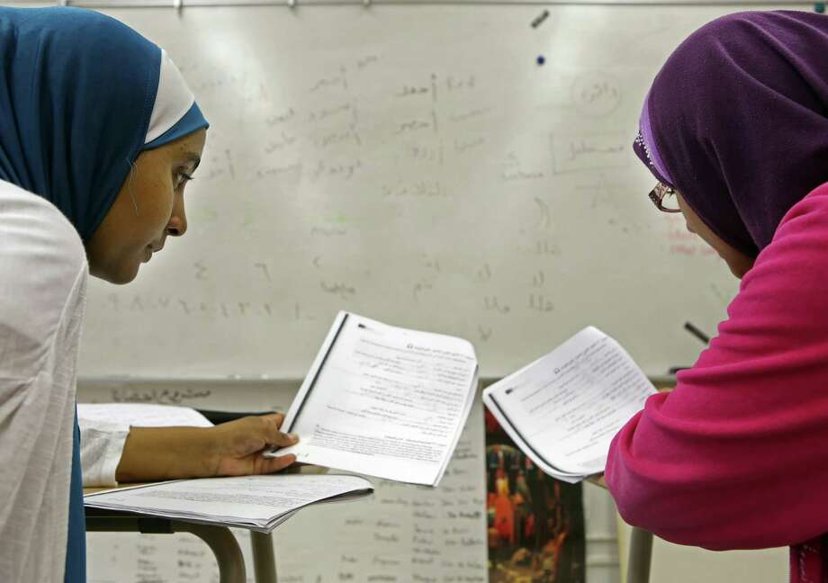 HISD students Sahar Fattani and Amina Wote review a vocabulary lesson in their Level 3 Arabic class at Bellaire High School. Photo: Mayra Beltran, Staff / © 2014 Houston Chronicle
