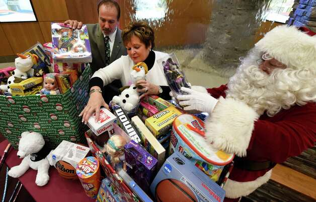 Lenny Ricchiutti, executive director of the Police Athletic League (PAL), left Paula Stopera, president/CEO CAPCOM FCU, center, and Nick Casey, dressed as Santa, gather new toys and gifts for the kick off of the Pitch in for PAL. Albany PAL provides more than 2,500 toys to needy children during the holidays each year with the help of companies such as CAP COM FCU and others. (Skip Dickstein/Times Union) Photo: SKIP DICKSTEIN / 00029437A
