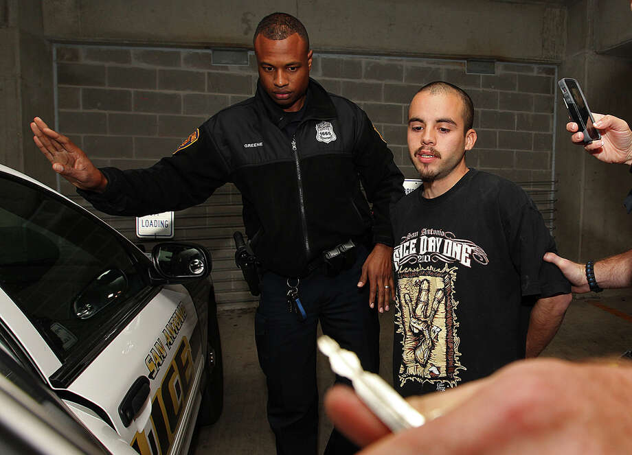 Zachary Gonzales is escorted out of San Antonio Police Deapartment Headquarters, Wednesday, Nov. 12, 2014. Gonzales was arrested earlier in the day on murder charges stemming from Tuesday's VIA bus shooting of Donovan Rae Arzola, 23. He was shot while riding the bus near downtown. Photo: JERRY LARA, San Antonio Express-News / © 2014 San Antonio Express-News