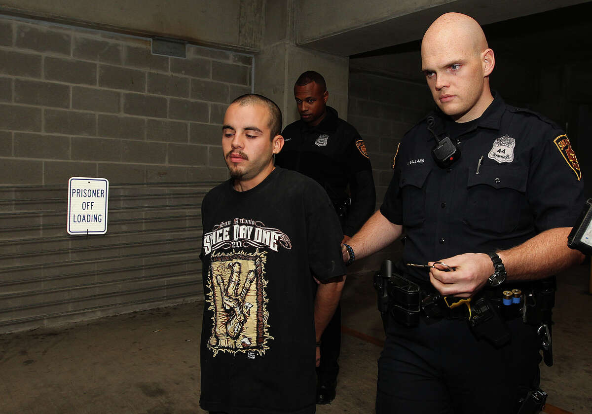 Zachary Gonzales is escorted out of San Antonio Police Deapartment Headquarters, Wednesday, Nov. 12, 2014. Gonzales was arrested earlier in the day on murder charges stemming from Tuesday's VIA bus shooting of Donovan Rae Arzola, 23. He was shot while riding the bus near downtown.