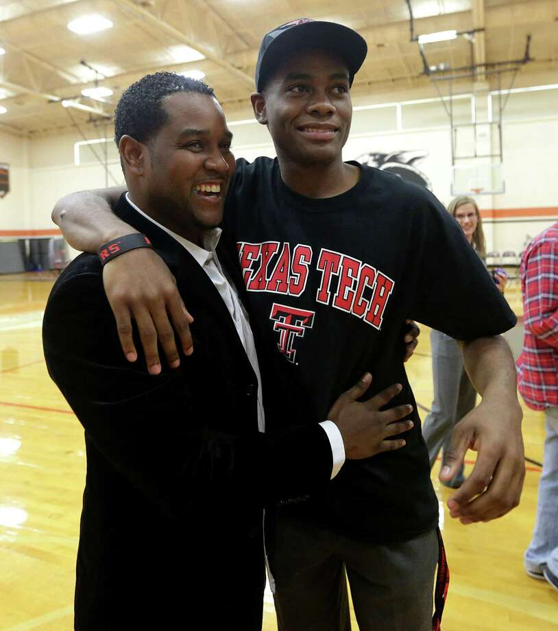 Jordan Jackson, right, gets a hug from his father, Eric, after signing a letter of intent to play basketball at Texas Tech. Photo: Billy Smith II, Staff / © 2014 Houston Chronicle
