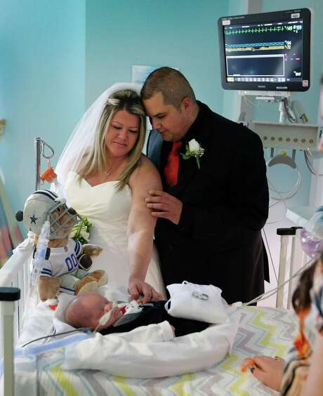 Kristi Warriner, left, and Justin Nelson look on at their son, J.J. after they were married in the neonatal intensive care unit of Cook Children's Medical Center  in Fort Worth, Texas on Tuesday, Nov. 11, 2014.  J.J. was born Sept. 2, about 15 weeks early, at 1 pound, 13 ounces, and has breathing problems due to underdeveloped lungs. His twin brother, Colt Austin Nelson, was stillborn.  The Nelsons are optimistic that they will be able to take their growing son home by Christmas. He now weighs more than 6 pounds. (AP Photo/The Fort Worth Star-Telegram, Ron T. Ennis)  MAGS OUT; (FORT WORTH WEEKLY, 360 WEST); INTERNET OUT Photo: Ron T. Ennis, MBI / The Fort Worth Star-Telegram