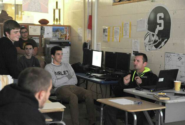 Schalmont High School football coach Joe Whipple, right, goes over game film with his team Wednesday, Nov. 12, 2014, in Rotterdam, N.Y. (Michael P. Farrell/Times Union) Photo: Michael P. Farrell / 00029455A