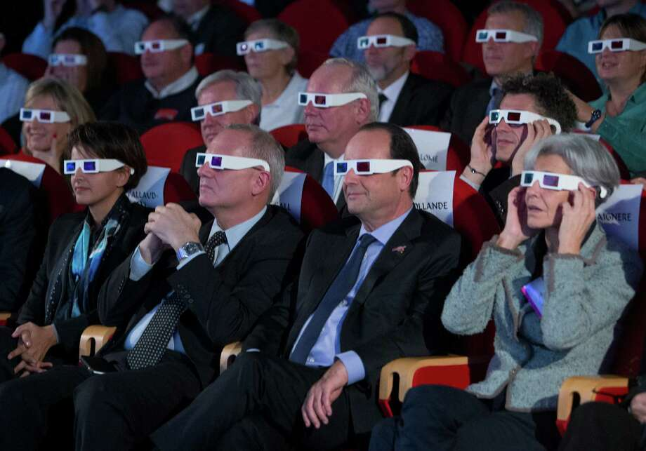 French National Centre for Space Studies (CNES) president Jean-Yves Le Gall, second left, French President Francois Hollande, center, and former French minister and astronaut Claudie Haignere, right, wear 3D glasses as they visit the Cite des Sciences at La Villette during a broadcast of the Rosetta mission as it orbits around comet 67/P Churyumov-Gersimenko in Paris,  Wednesday, Nov. 12, 2014. Hundreds of millions of miles from Earth, a European spacecraft made history Wednesday by successfully landing on the icy, dusty surface of a speeding comet — an audacious first designed to answer big questions about the universe. (AP Photo/Jacques Brinon, Pool) Photo: Jacques Brinon, POOL / AP POOL