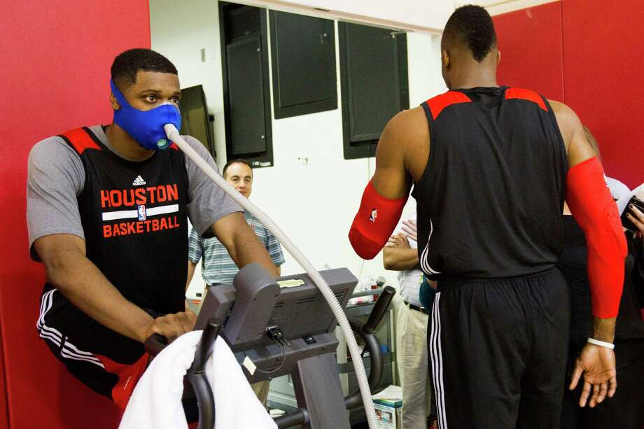 Houston Rockets forward Terrence Jones, left, works out on a stationary bicycle as center Dwight Howard walks off the court following the first practice of Rockets training camp at Toyota Center Tuesday, Sept. 30, 2014, in Houston. ( Brett Coomer / Houston Chronicle ) Photo: Brett Coomer, Staff / © 2014 Houston Chronicle
