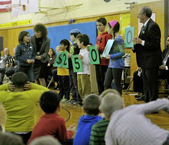 Jane Foley, second from left, senior vice president of the Milken Family Foundation with the help of Rosendale Elementary School students, shows how much money will be given to the recipient of the Milken Educator Award during an assembly at the school on Wednesday, Nov. 12, 2014, in Niskayuna, N.Y.  Fourth grade teacher Roseann Maurantonio was given the award.  (Paul Buckowski / Times Union) Photo: Paul Buckowski / 00029448A