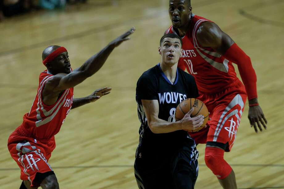 Minnesota Timberwolves' Zack Levine, center (8) runs past Houston Rockets' Dwight Howard, (12), right, and Jason Terry (31) as he prepares to attempt a shot during the first half of an NBA basketball game in Mexico City, Wednesday, Nov. 12, 2014. (AP Photo/Dario Lopez-Mills) Photo: Dario Lopez-Mills, STF / AP