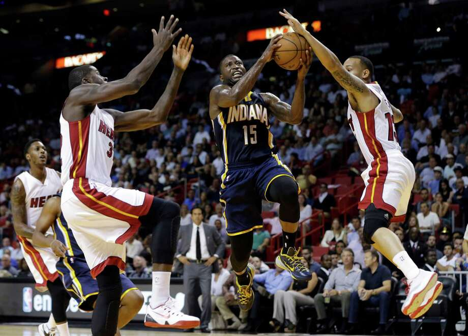 Indiana Pacers' Donald Sloan (15) shoots as Miami Heat's James Ennis, left, and Shabazz Napier (13) defend in the first half of an NBA basketball game, Wednesday, Nov. 12, 2014, in Miami. (AP Photo/Lynne Sladky) Photo: Lynne Sladky, STF / AP