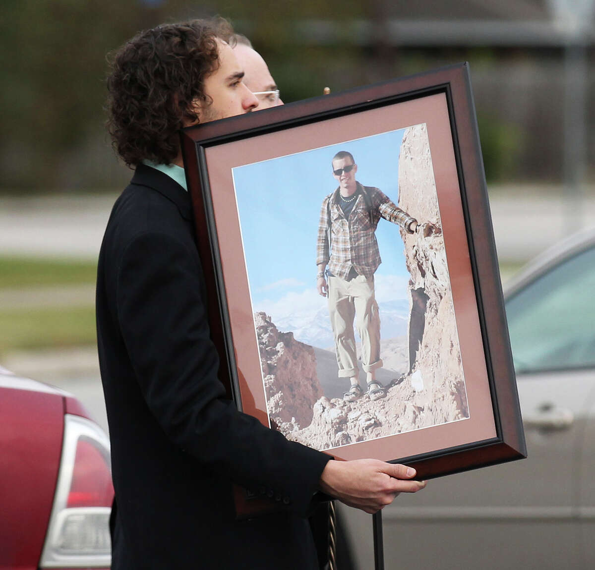 An image of Cameron Redus is carried away after a funeral service for Redus at Memorial Baptist Church in Baytown, Texas on Thursday, Dec. 12, 2013. Redus died of gunshot wounds from a University of Incarnate Word campus policeman last Friday. Family and friends gathered at the church to pay their last respects to the 23-year-old. Green was Redus' favorite color and classmates made 700 ribbons to pass out to mourners at the service. (AP Photo/San Antonio Express-News, Kin Man Hui)**MAGS OUT NO SALES SAN ANTONIO OUT**