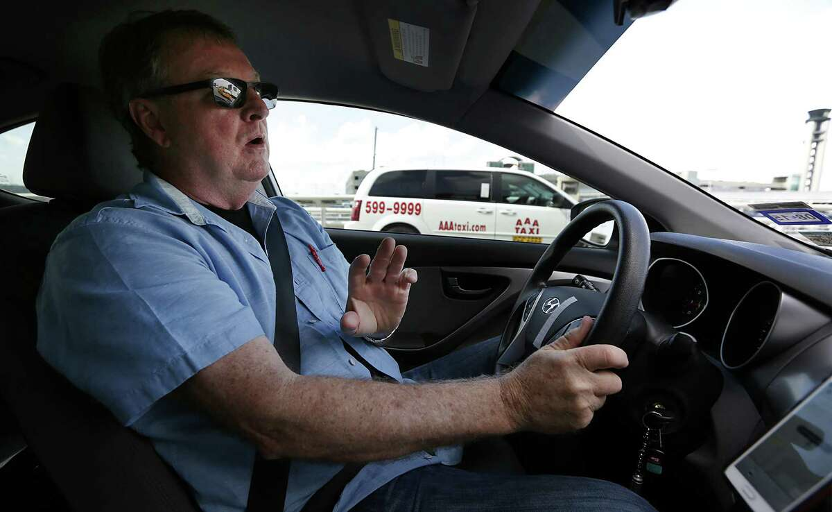 Dale Blankenship, an Uber driver, drives around the San Antonio International Airport, as a taxi passes him. Wednesday, Oct. 8, 2014.