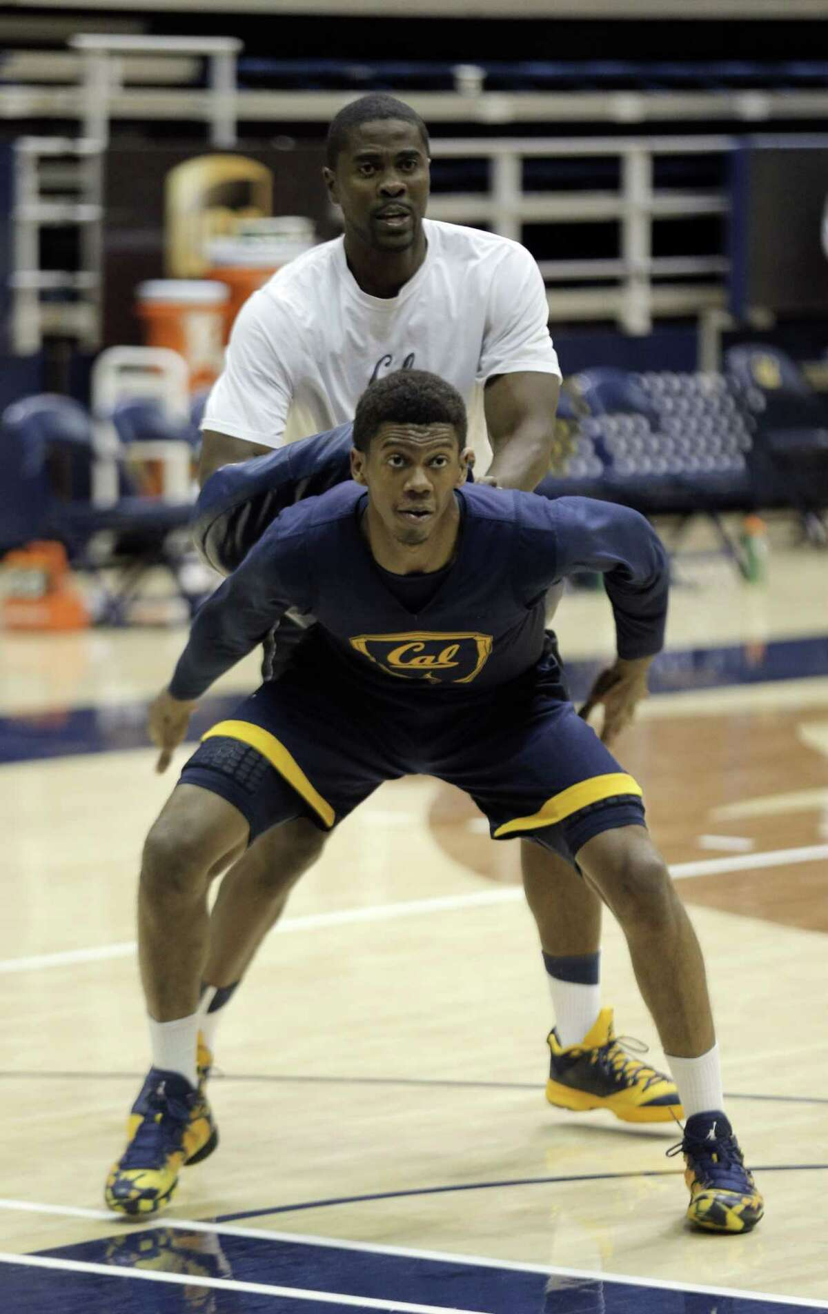 Tyrone Wallace (3) works with assistant coach Jon Harris during the Cal men's basketball practice at Haas Pavilion in Berkeley, Calif., on Tuesday, November 11, 2014.
