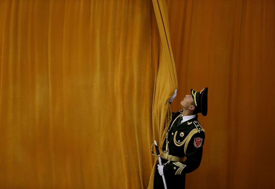 A Chinese People's Liberation Army soldier closes a curtain as preparations for a welcome ceremony held by Chinese President Xi Jinping for visiting Mexican President Enrique Pena Nieto at the Great Hall of the People in Beijing Thursday, Nov. 13, 2014. (AP Photo/Andy Wong) Photo: Andy Wong, Associated Press